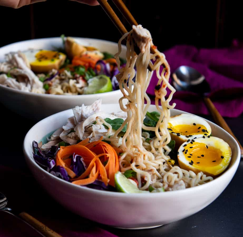 Chopsticks lifting noodles from a bowl of leftover turkey ramen soup