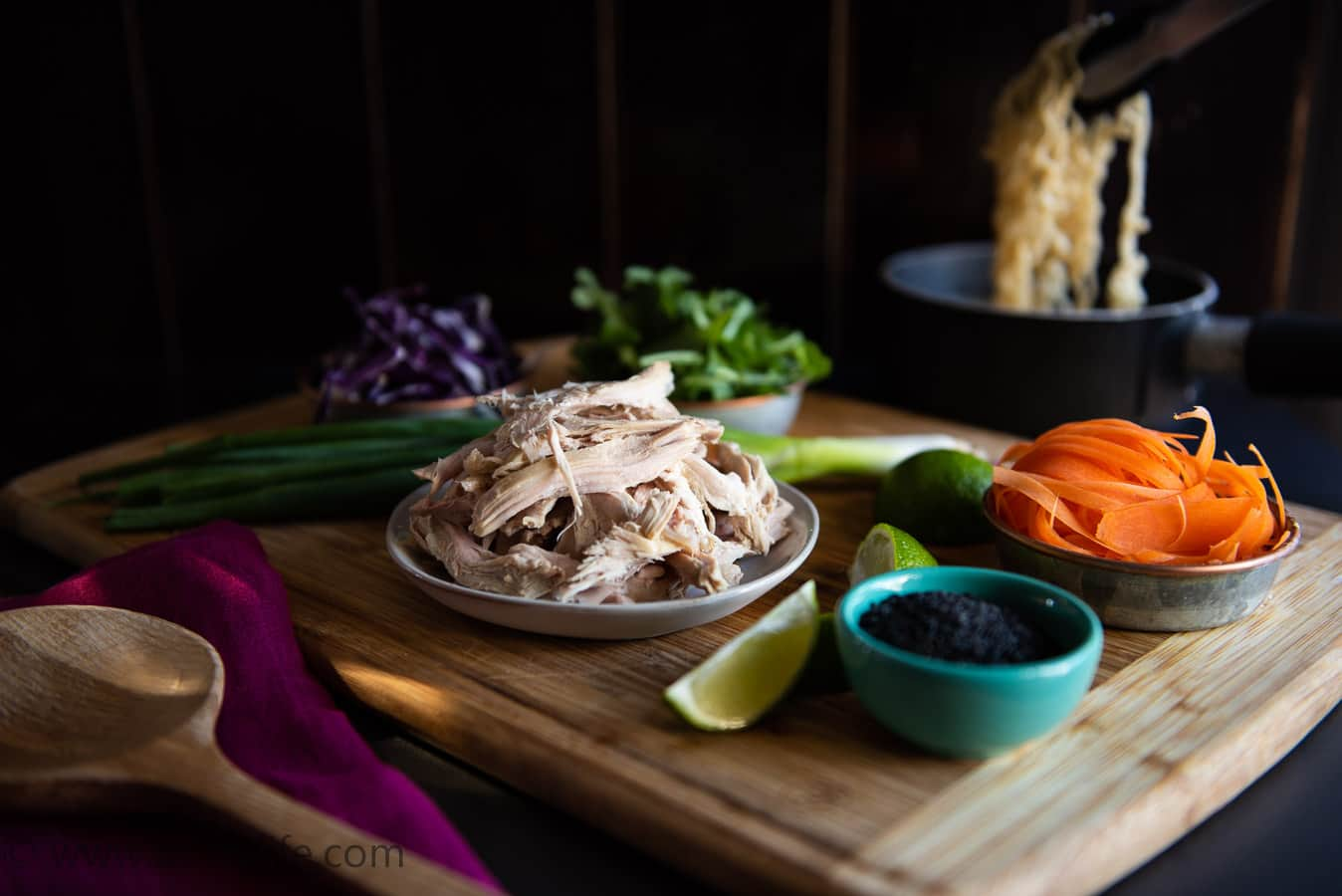 Wooden cutting board with ingredients for leftover turkey ramen soup