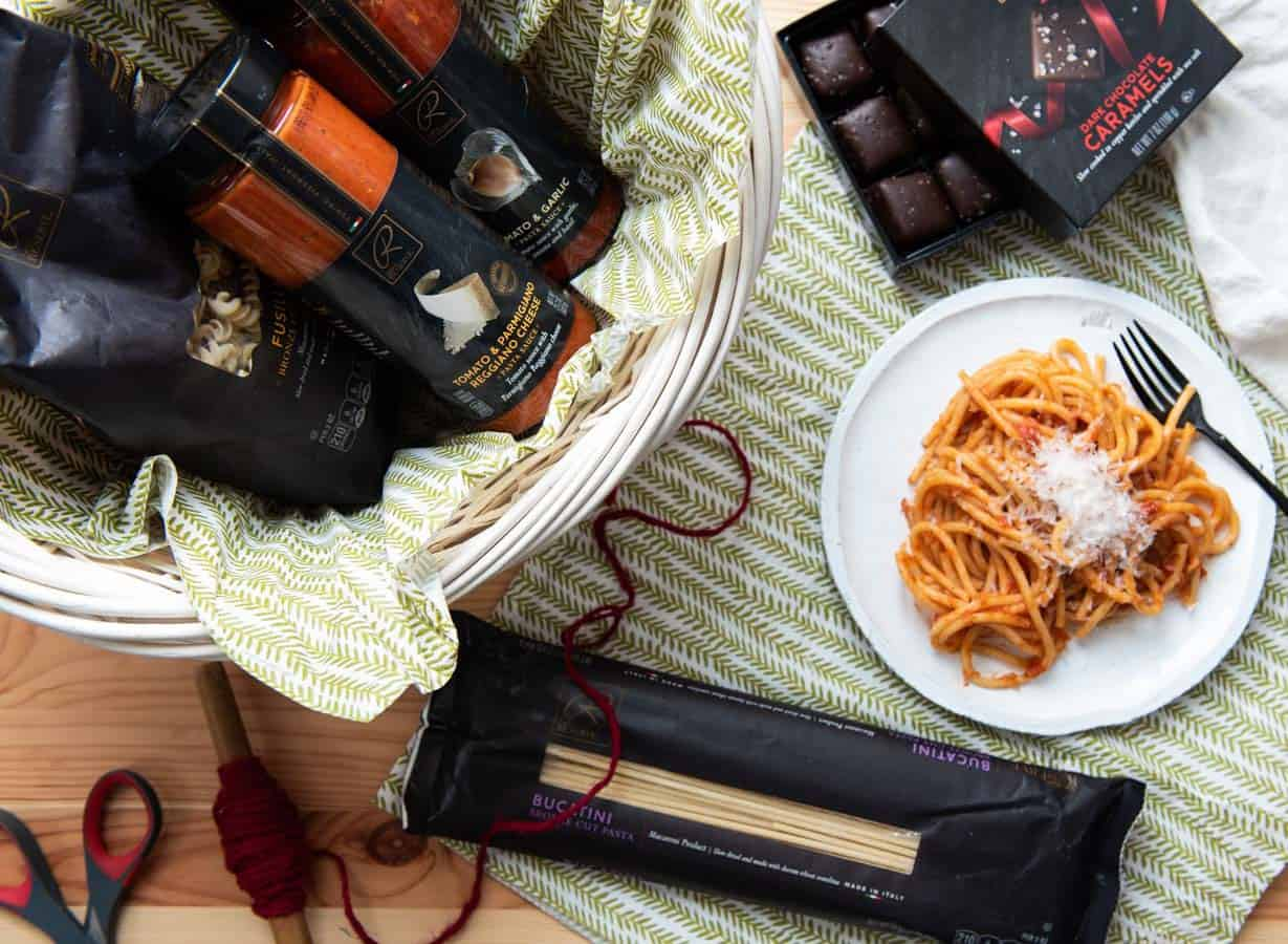 Plate of pasta next to a gift basket of dried pastas and sauces