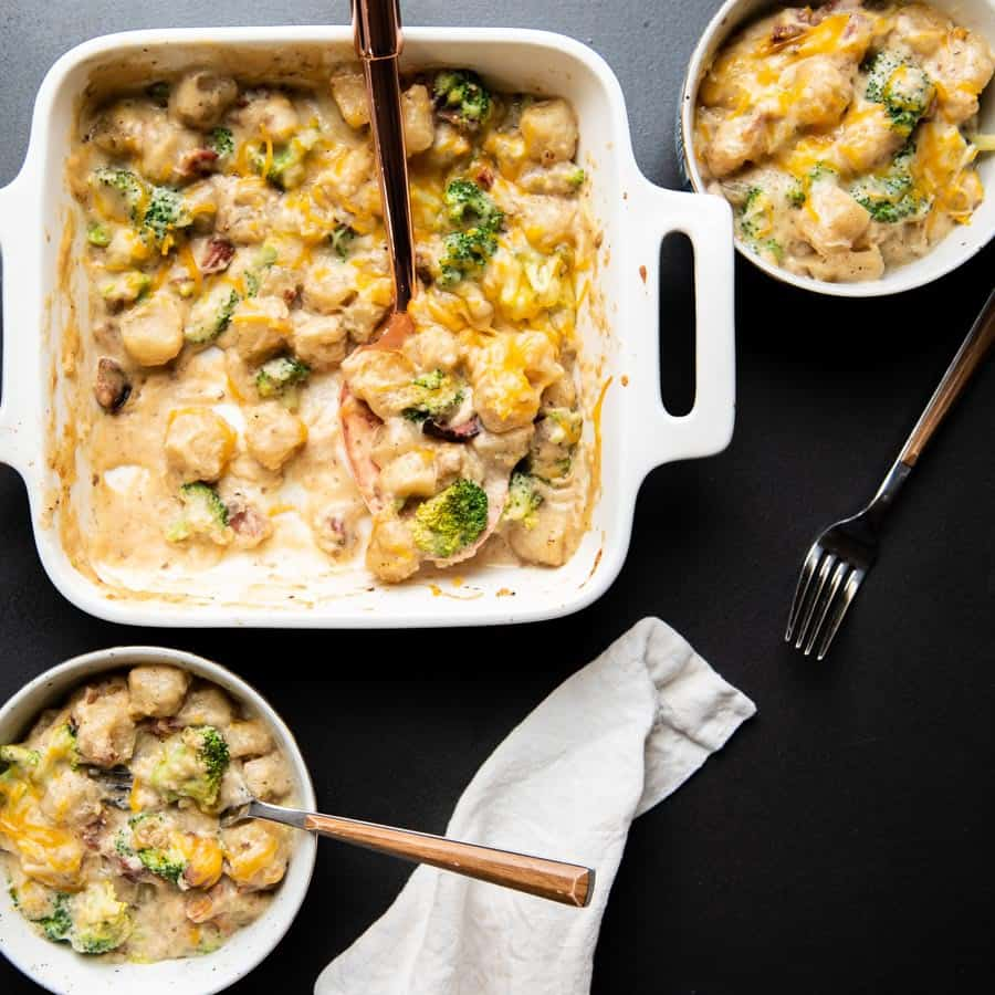 white casserole dish with cheesy cauliflower gnocchi scooped into two bowls