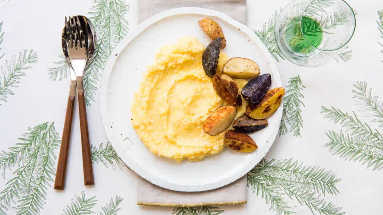White plate with creamy polenta and roasted potato wedges on a pine bough printed placemat
