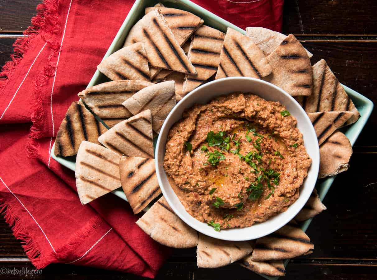 bowl of muhammara roasted red pepper and walnut dip on a platter of grilled pita bread cut into triangles on a red napkin