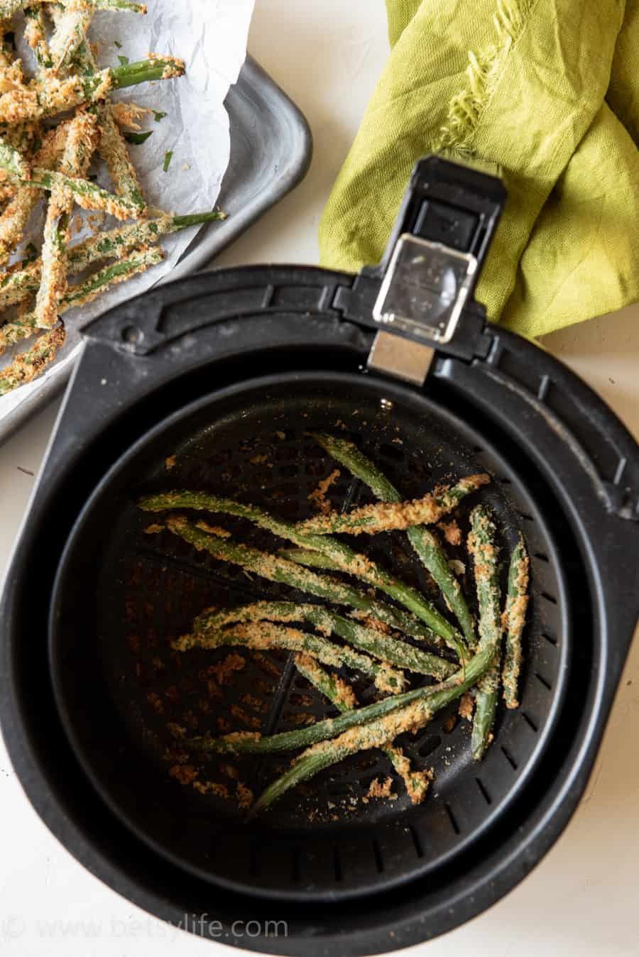 Air fryer basket filled with crispy green bean fries