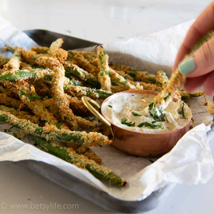 hand dipping air fryer green bean fries into white dipping sauce
