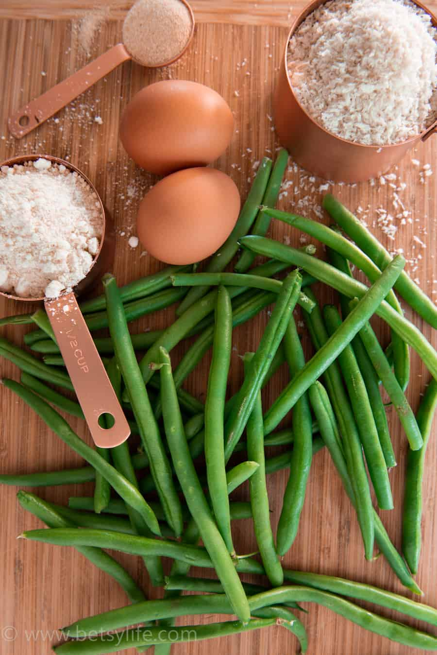 green beans, parmesan cheese, eggs, breadcrumbs and garlic powder on a wood cutting board