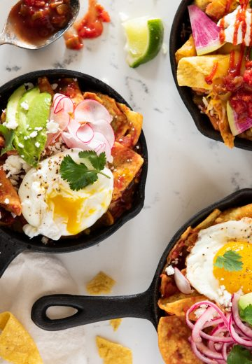 three small skillets filled with chilaquiles rojas and topped with different toppings