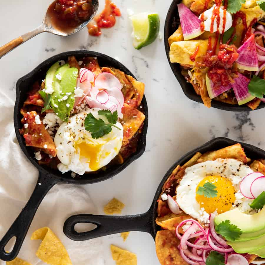 three skillets of chilaquiles rojas with different toppings