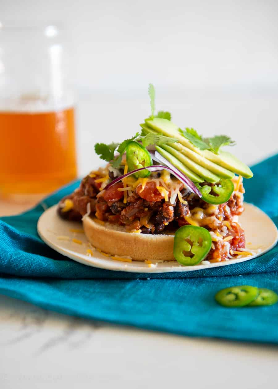 Southwestern style spicy sloppy joe piled high on a bun with melted cheese, sliced avocados, jalapenos and red onions next to a glass of beer