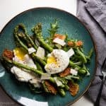 blue plate with roasted asparagus, poached eggs, crispy prosciutto, and shaved parmesan
