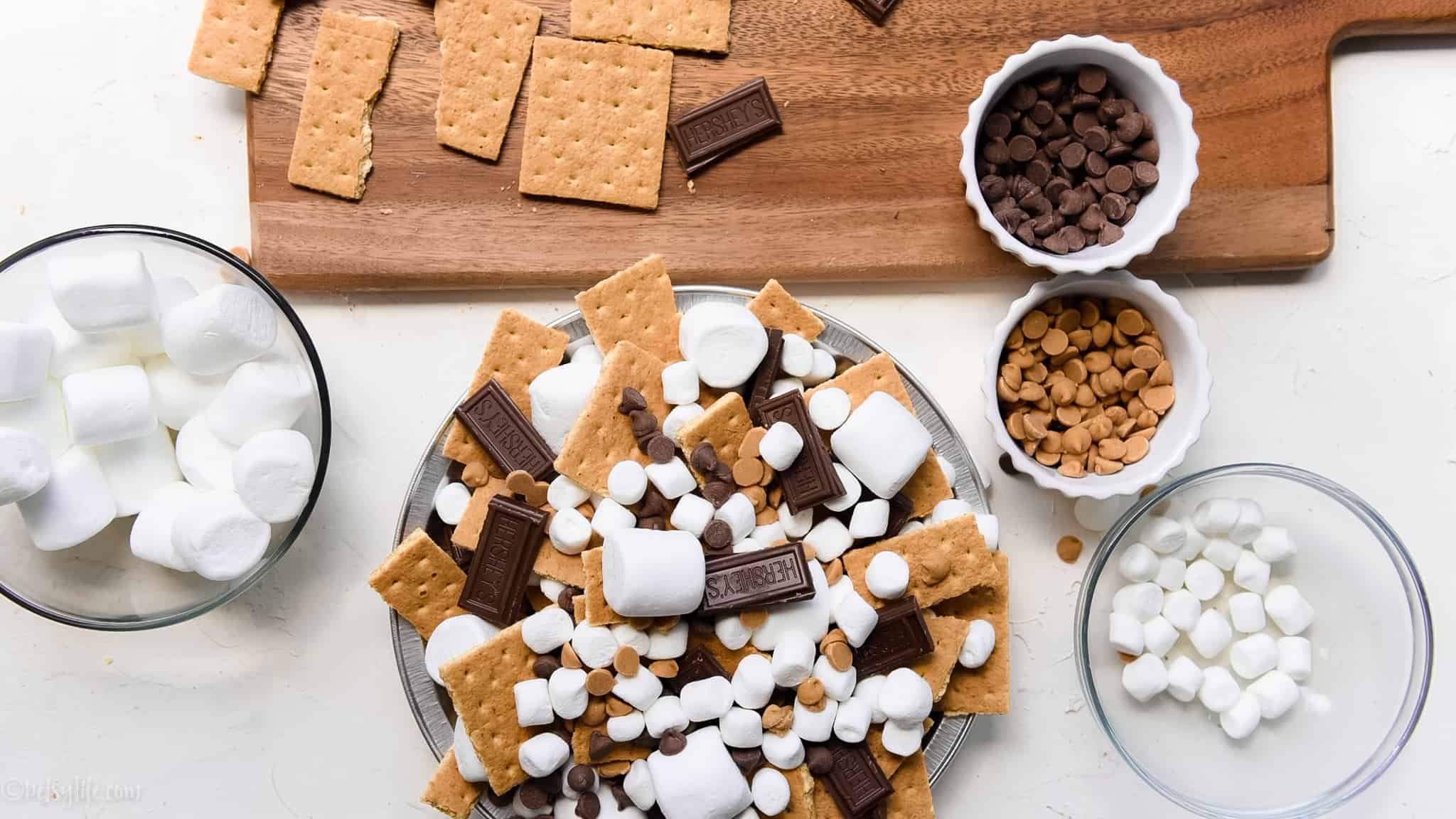 preparing smores nachos. Bowls of chocolate chips, marshmallow and graham crackers on a board