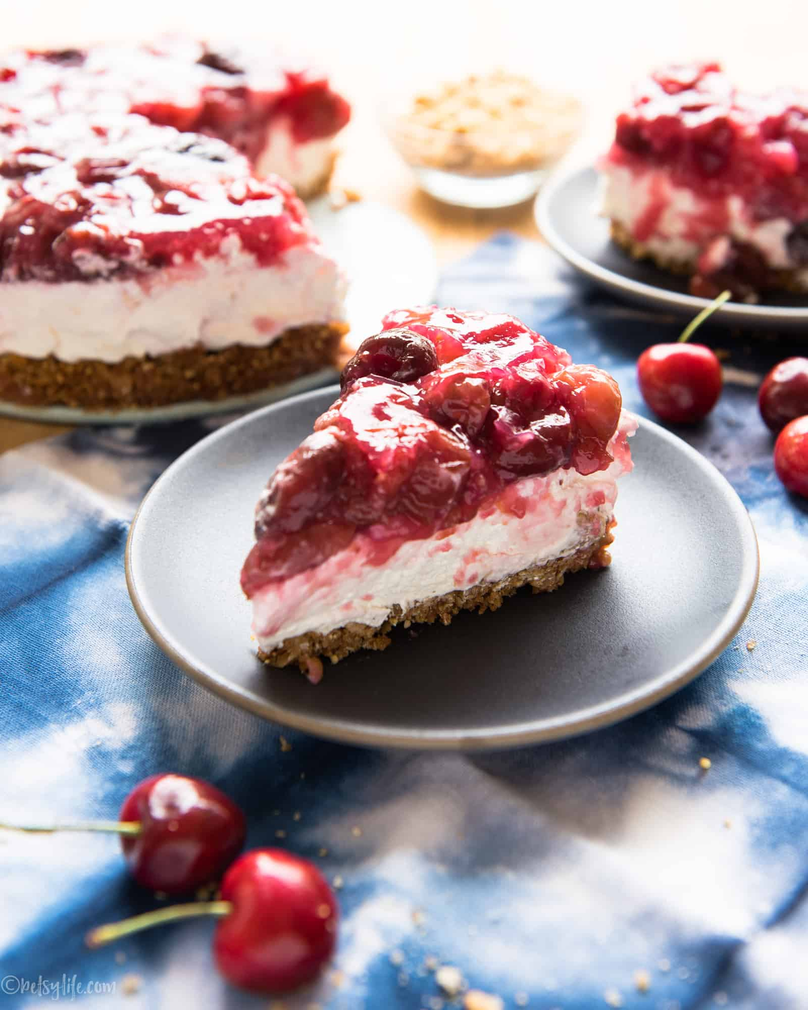slice of cherry cream pie on a gray plate next to whole pie