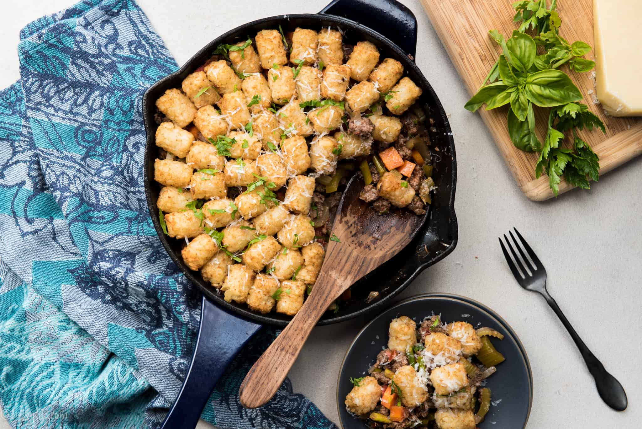 tater tot casserole with veggies in a skillet with a wooden spoon. Serving on a dark plate to the side