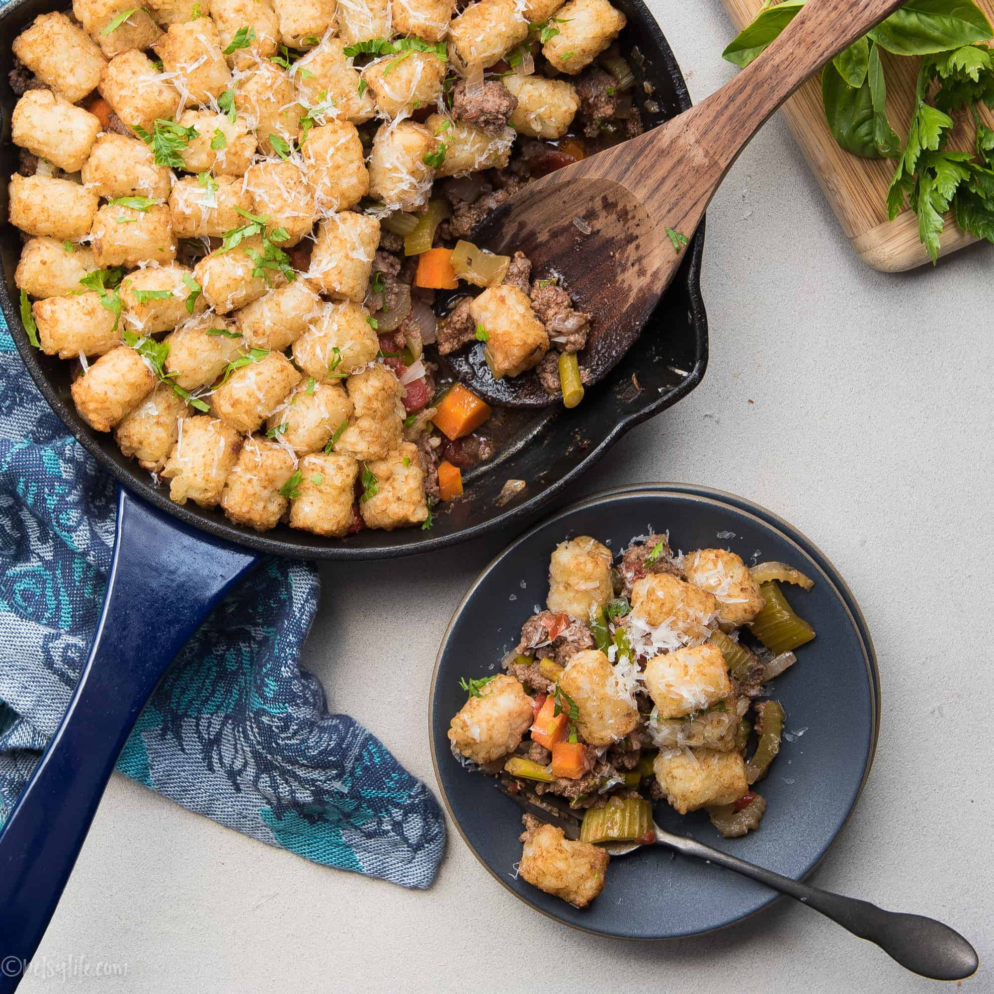 serving of tater tot casserole on a dark plate next to a skillet full of casserole