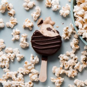 Chocolate covered ice cream bar surrounded by popcorn melting