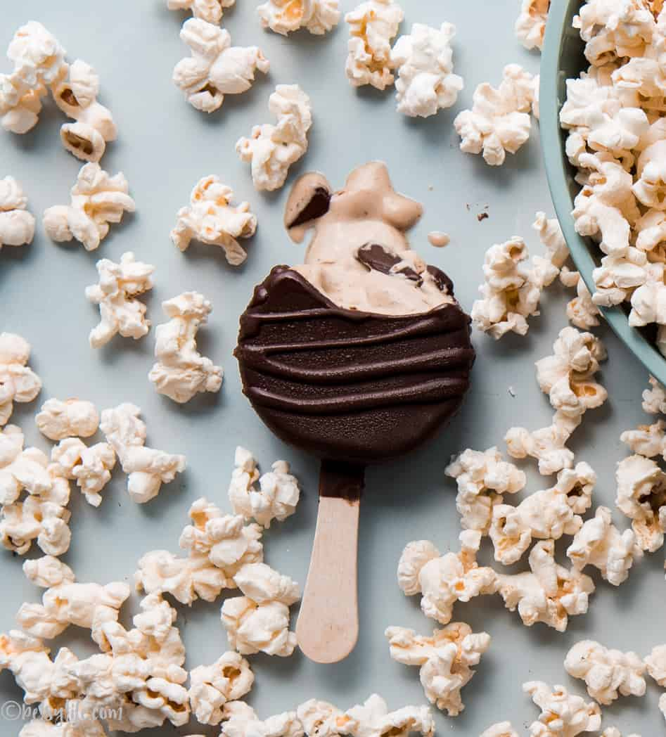 Chocolate covered plant based frozen dessert bar melting. Surrounded by popcorn