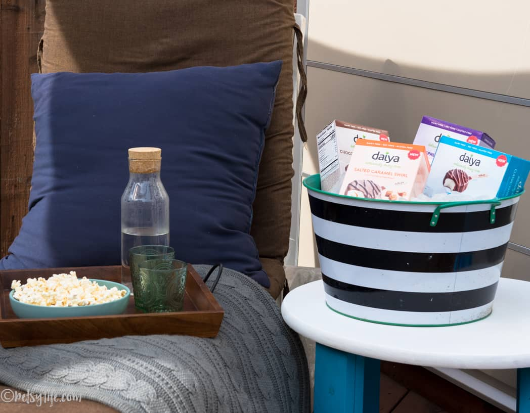 outdoor chair set up with tray of snacks and cooler bucket full of frozen dessert bars