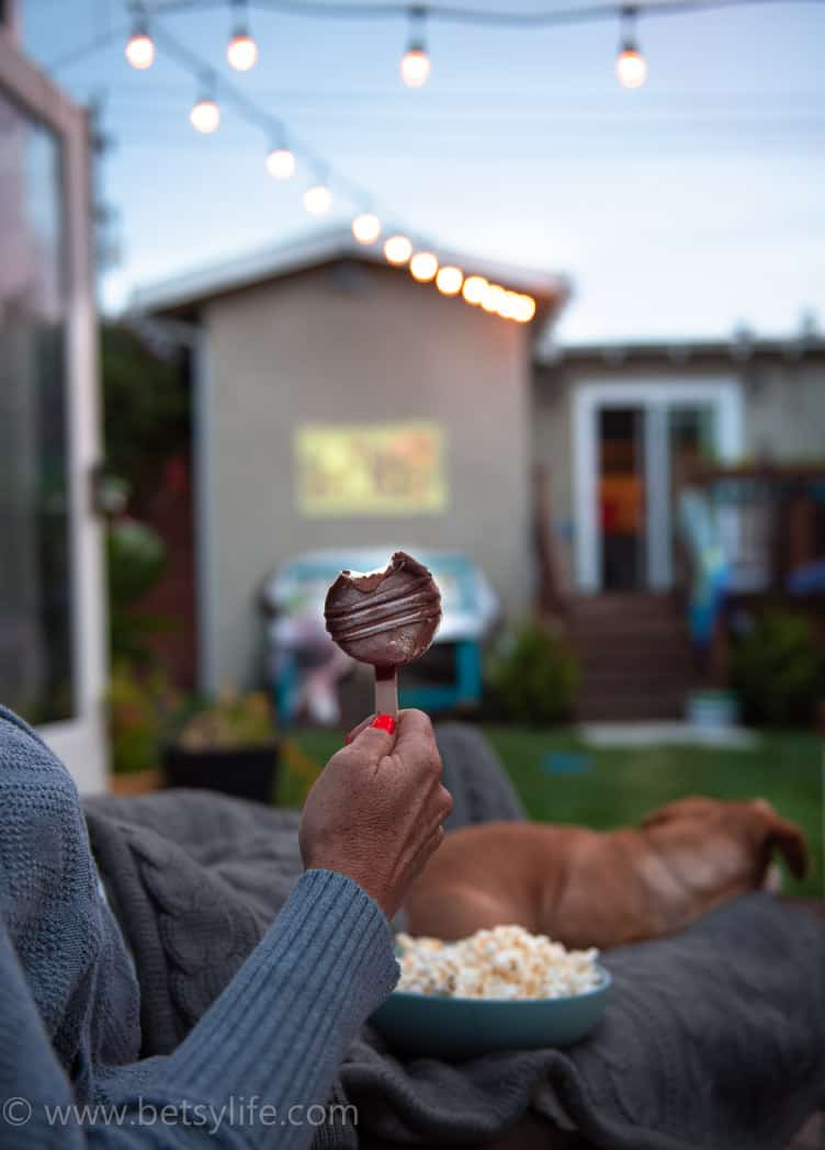 frozen dessert bar being enjoyed outside while watching a movie at dusk