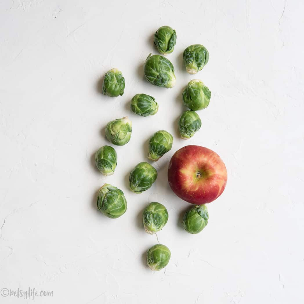 Brussels Sprouts and a red apple on a white background