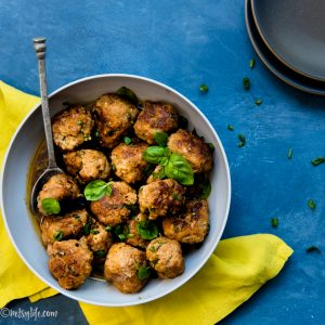 bowl of pork meatballs on a blue background