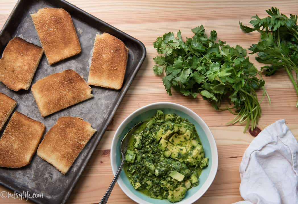 bowl of avocado and chimichurri next to a sheet pan of toast and two bunches of herbs