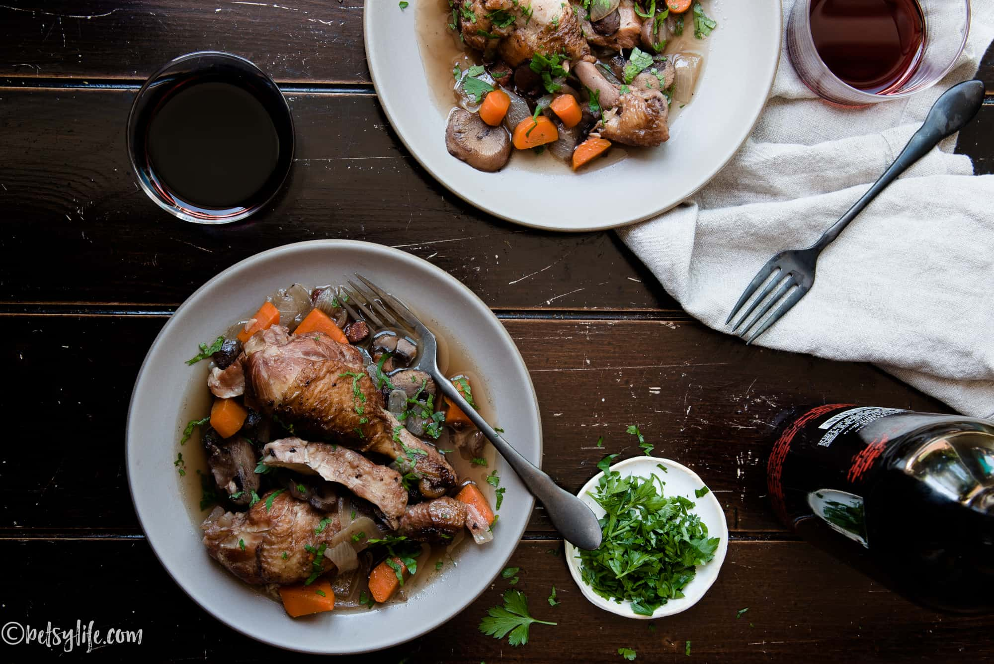Two plates of coq au vin next to wine bottle and two glasses