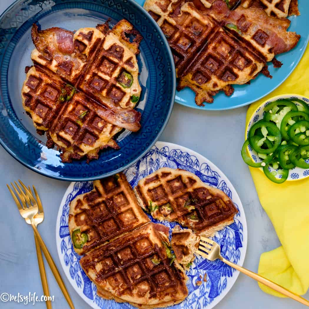 Three blue plates with savory waffles with bacon and jalapeños baked in next to a bowl of jalapeños