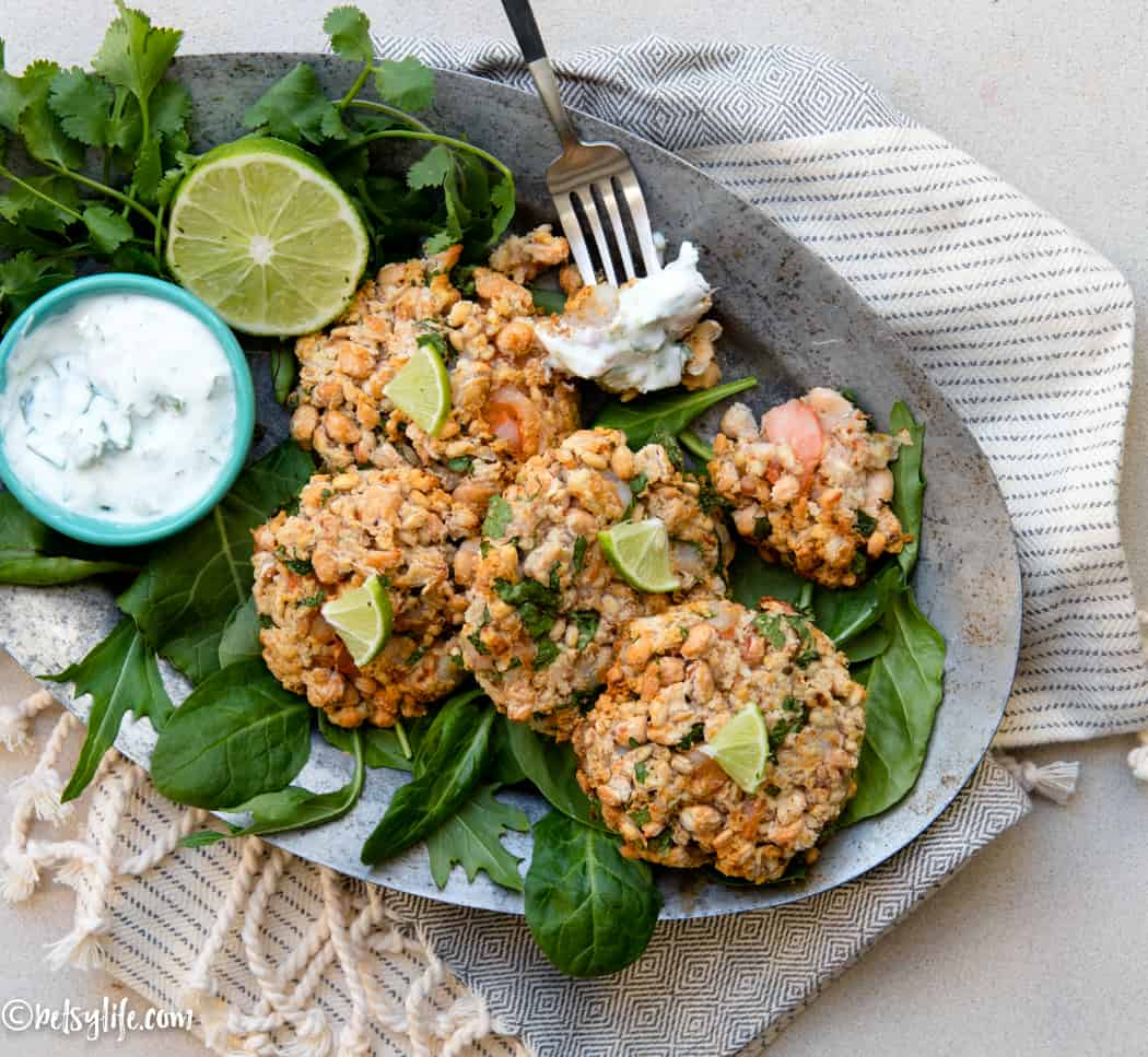 metal platter with white bean and shrimp patties, greens, limes and white sauce