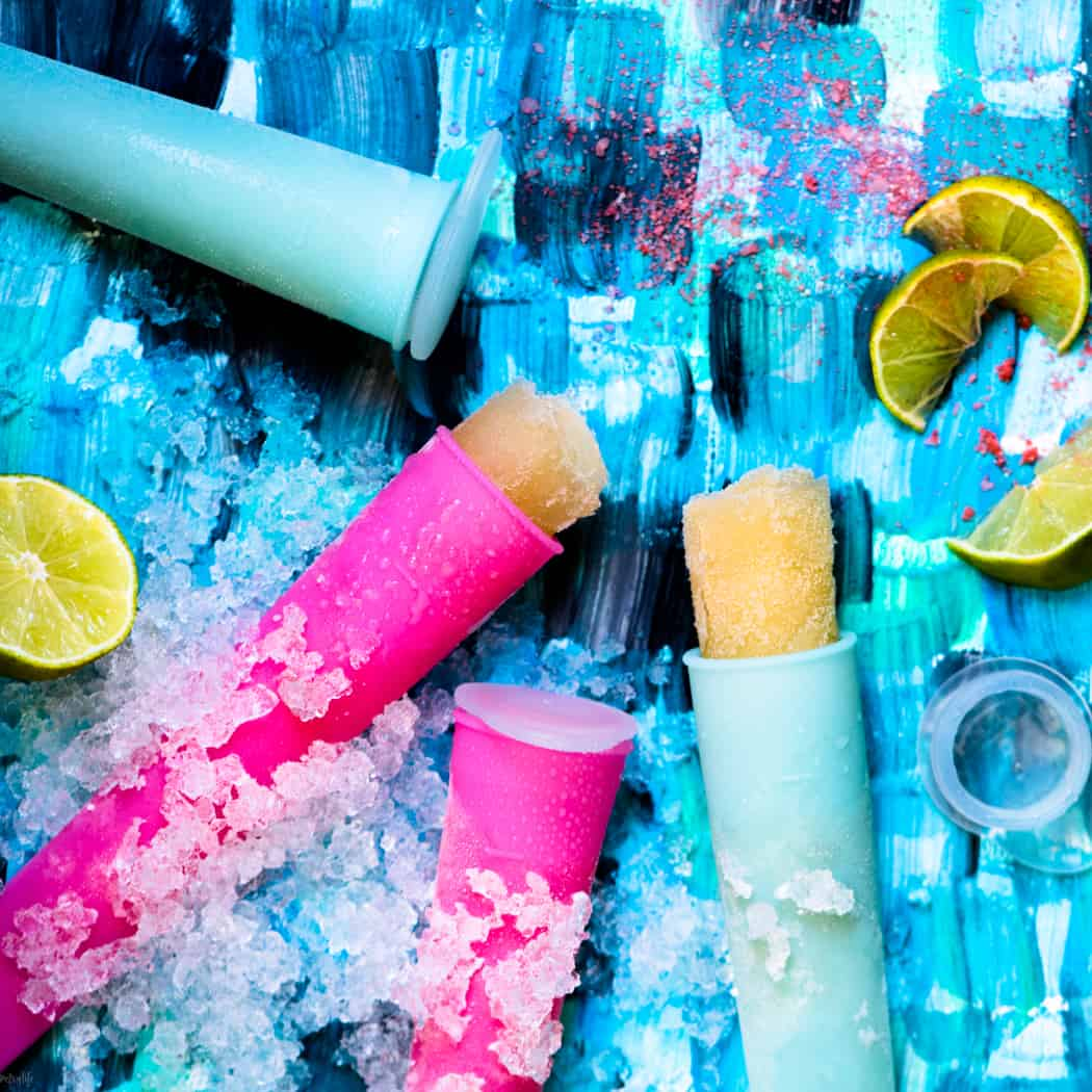 Pink and blue margarita popsicles on a blue background with ice and limes