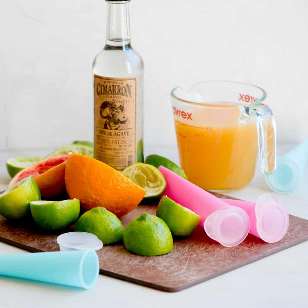 limes, oranges and tequila next to a pitcher of juice and empty popsicle molds