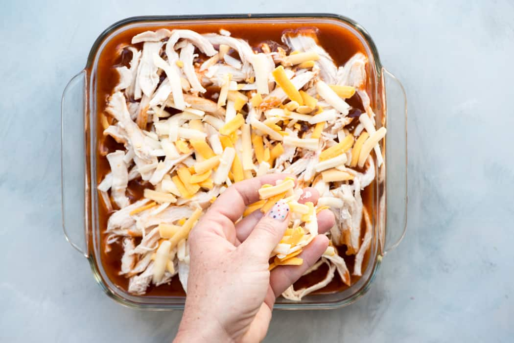 hand spreading shredded cheese over chicken tamale casserole before baking