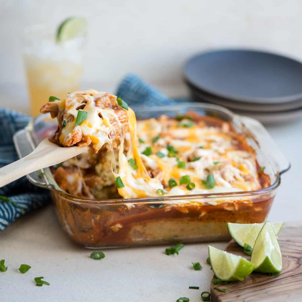 Wooden spoon scooping a cheesy serving from a casserole dish