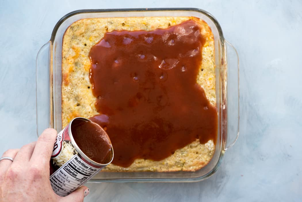 can of red sauce being poured over a baked dish of cornbread