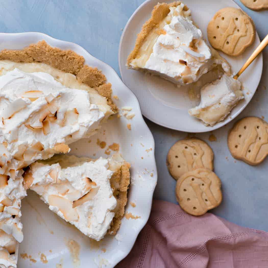 Sliced coconut cream pie next to a plate and girl scout cookies