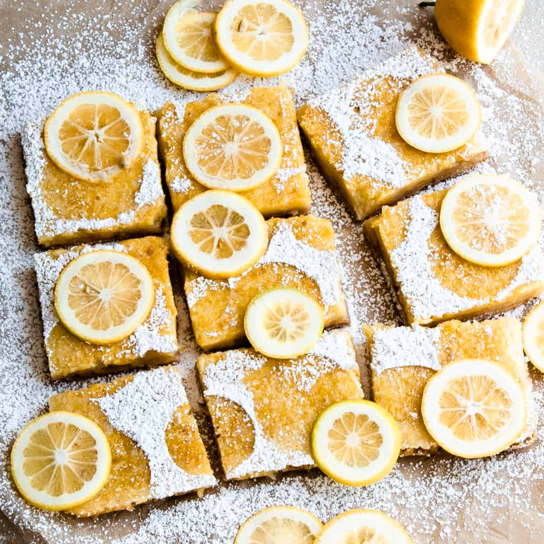 Lemon bars topped with powdered sugar and lemon slices