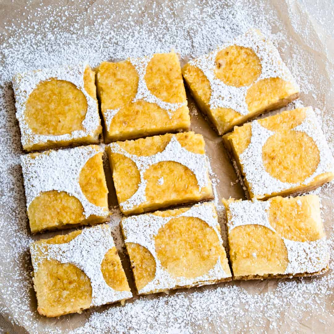 Lemon bars dusted with powered sugar in a circular pattern