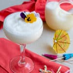 Frozen coconut water cocktail in a coupe glass with flowers and a paper umbrella