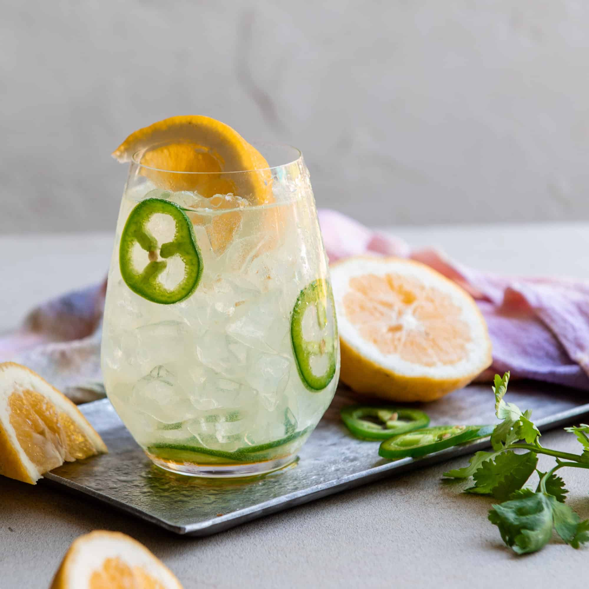 Coconut water and lemonade cocktail with sliced jalapenos and lemon wedges