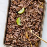 Sheet pan filled with shredded beef and limes with two gold forks