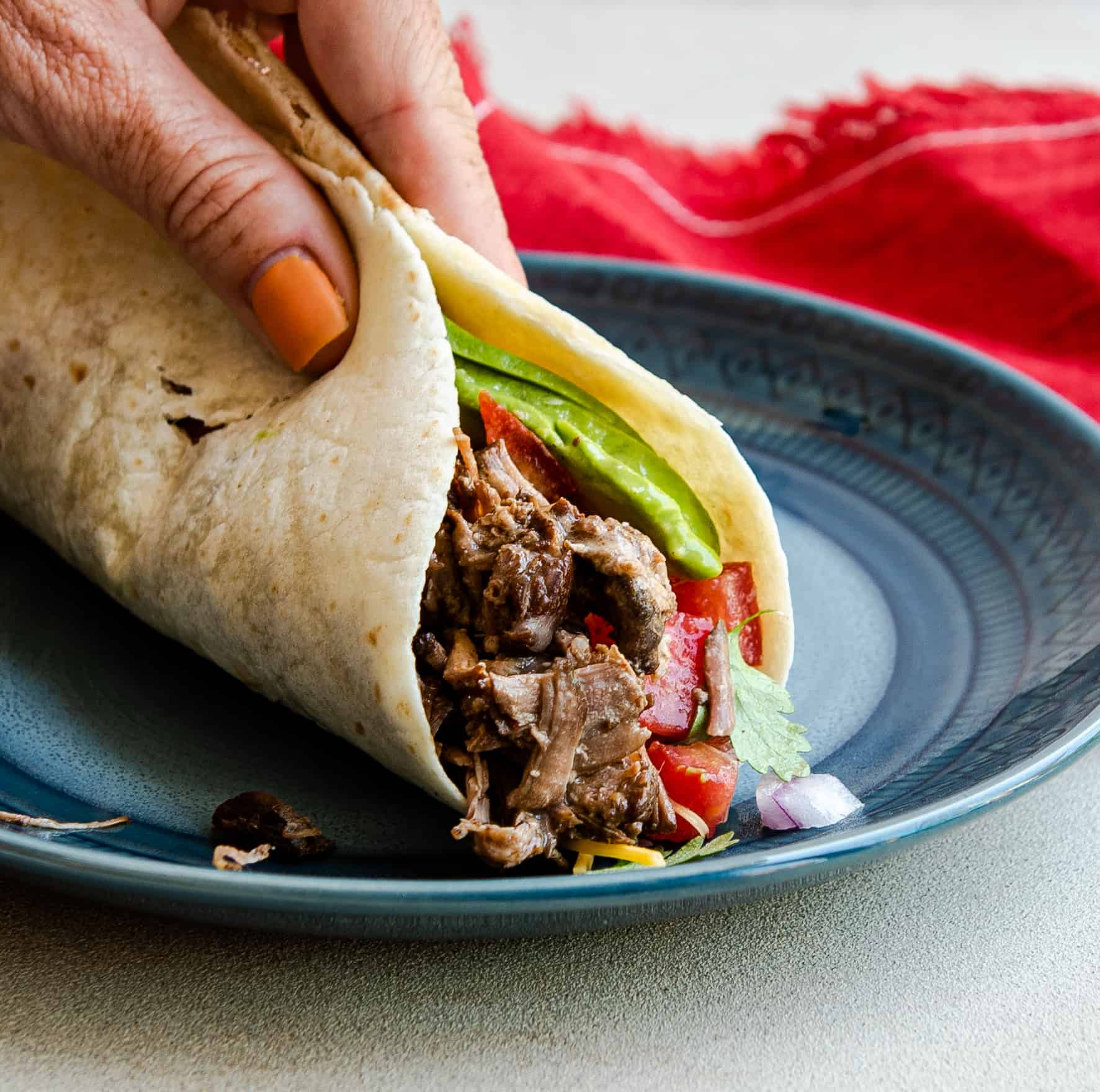 hand folding a taco on a blue plate with a red napkin