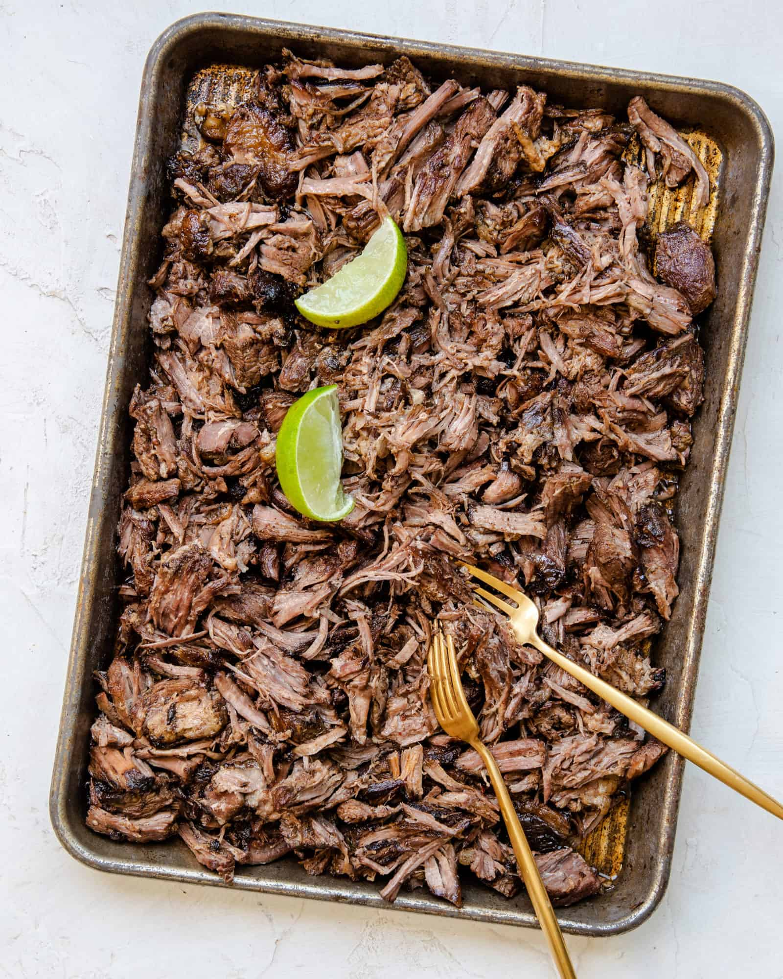 Sheet pan covered in shredded beef and limes with two gold forks